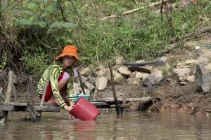 A photo of a Vietnamese woman on the Mekong River Delta.