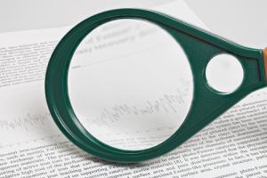 Magnifying glass on academic paper image via Shutterstock